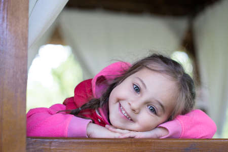 beautiful little girl leaning over railing, looking smiles and looks at you Stockfoto