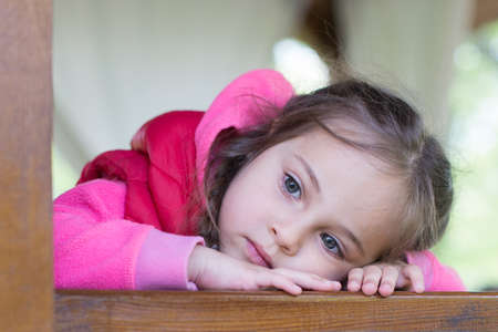 beautiful little girl leaning over railing looking thoughtfully into the distance
