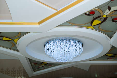 elegant crystal chandelier. White ceiling with windshields