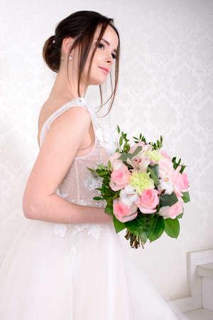 Slim beautiful woman wearing luxurious wedding dress over white studio background. Gorgeous bride holding flowers