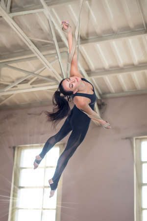 Beautiful girl aerial gymnast. Circus artist on the aerial straps with Strong muscles on background the window