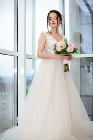 Slim beautiful woman wearing luxurious wedding dress near the panoramic window. Gorgeous bride holding flowers Stockfoto