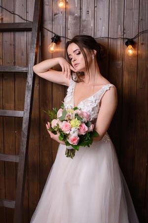 Slim beautiful woman wearing luxurious wedding dress on wooden background. Gorgeous bride holding flowers Stockfoto