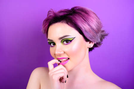 Flirt girl. Sexy girl with short hair. Portrait of a woman with bright colored hair, all shades of purple. Beautiful lips and makeup. . Professional coloring. professional makeup