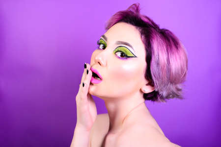 Shock reaction. Sexy girl with short hair. Portrait of a woman with bright colored hair, all shades of purple. Beautiful lips and makeup. . Professional coloring. professional makeup Stockfoto