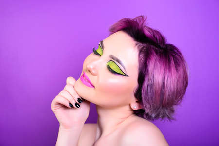 Sexy girl with short hair. Portrait of a woman with bright colored hair, all shades of purple. Beautiful lips and makeup. Professional coloring. professional makeup