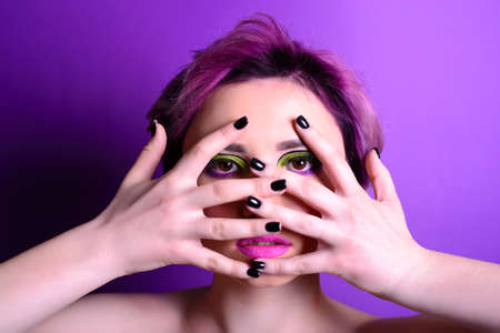 Looking through fingers. Sexy girl with short hair. Portrait of a woman with bright colored hair, all shades of purple. Beautiful lips and makeup. . Professional coloring. professional makeup