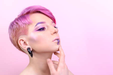 Sexy girl with short hair. Portrait of a woman with bright colored hair, all shades of pink. Beautiful lips and makeup. Professional coloring. professional makeup Stockfoto