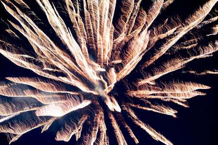 A few volleys of festive fireworks in the night sky, red-yellow.