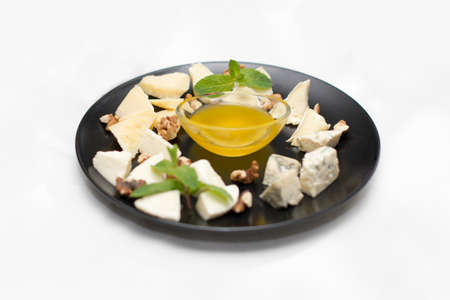 cheese platter with honey and nuts on white restaurant plate isolated on white background Stockfoto