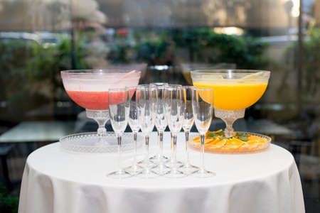 A pyramid of glasses. Orange and pink Champagne with fruits.