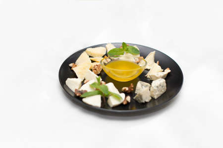 cheese platter with honey and nuts on white restaurant plate isolated on white background.