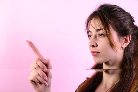 Portrait of a pretty woman standing and pointing finger away at copy space over pink background.