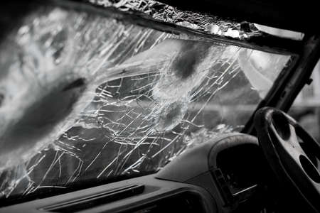 Bullet hole on a car windshield. Car window after a raid has a bullet hole. Broken glass. Bullet holes in a front windshield. Broken Windshield.