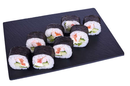 Traditional fresh japanese sushi futomaki on black stone Futomaki with Tuna on a white background. Roll ingredients: tuna, philadelphia cheese, cucumber, tomato, lettuce, nori, rice