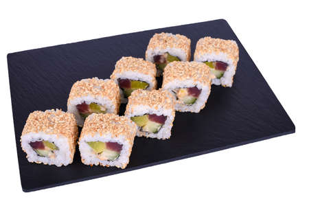 Traditional fresh japanese sushi rolls on a black stone Theca Spicy on a white background. Roll ingredients: tuna, daikon radish, cucumber, spicy sauce, nori, rice, white sesame seeds