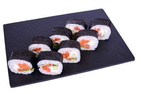 Traditional fresh japanese sushi futomaki on black stone Futomaki Syake on a white background. Roll ingredients: salmon, philadelphia cheese, cucumber, bell pepper, lettuce, nori, rice.
