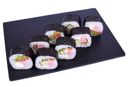 Traditional fresh japanese sushi futomaki on black stone Futomaki Yakito on a white background. Roll ingredients: ham, philadelphia cheese, cucumber, bell pepper, lettuce, nori, rice.