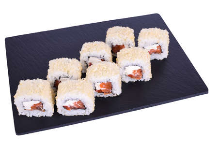 Traditional fresh japanese sushi rolls on a black stone Caesar with Salmon Roll on a white background. Roll ingredients: salmon, philadelphia, tomato, nori, rice, panko crackers.