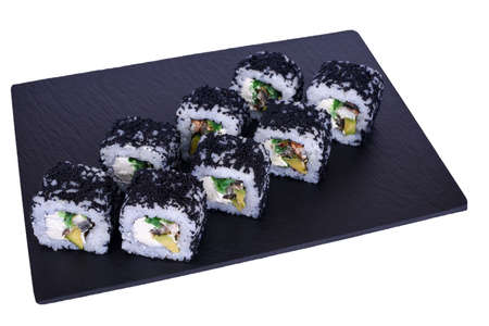 Traditional fresh japanese sushi rolls on a black stone Murugai on a white background. Roll ingredients: algae hiyashi, nori, rice, avocado, izumai perch, philadelphia cheese.
