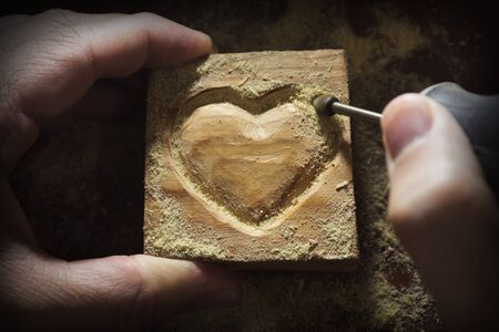 heart hard work: carving wood in heart shape