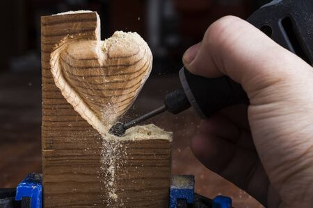 carving tool: Carving wood in heart shape with rotary tool Stock Photo