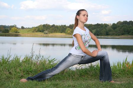 The young girl does physical exercises on a nature photo