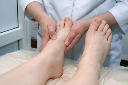 The masseur makes massage of legs in a massage-room photo