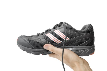footgear: black running shoe in the hand isolated on white Stock Photo