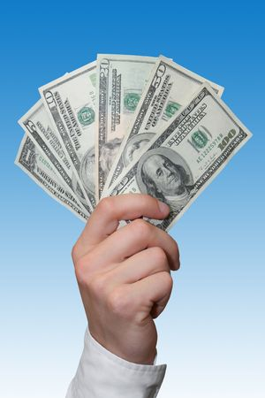 American dollars in a hand over blue background Stock Photo - 4715105