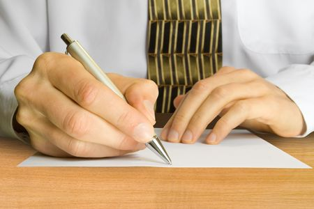 Businessman writes a pen on an empty paper photo