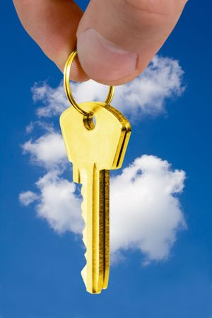 key in fingers over blue background. mortgage concept