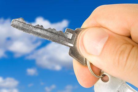 hand holds a key over blue sky Stock Photo - 5021763
