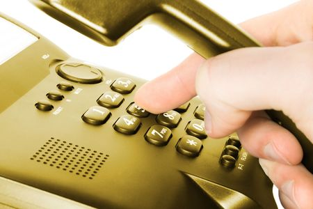 finger and keypad. dialing on gold telephone.  photo