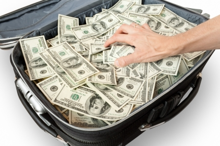 open suitcase: greed - lot of money in a suitcase with hand Stock Photo