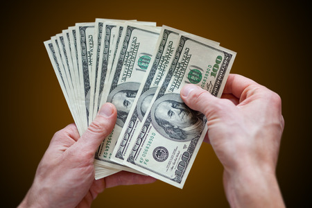 man holding money dollars in the hands Stock Photo
