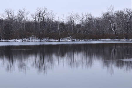 Winter landscape, lake among forest trees, trees are reflected in the water. There is snow on the ground, but the water in the lake is not frozen yet 写真素材