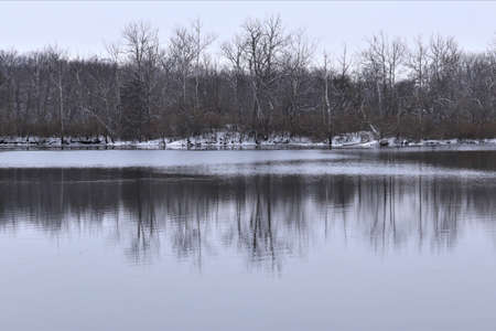 Winter landscape, lake among forest trees, trees are reflected in the water. There is snow on the ground, but the water in the lake is not frozen yet