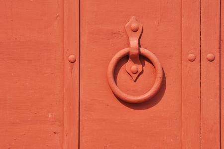 doorhandle: Red painted old iron door with circle doorhandle