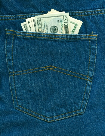 Dollars in dark blue jeans back pocket photo
