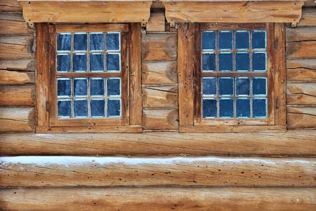 Weathered log house wall with window photo