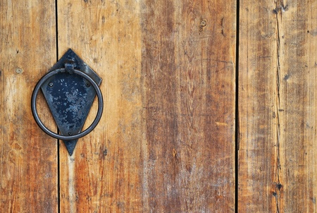 Closeup image of old wooden door with circle iron doorhandle photo