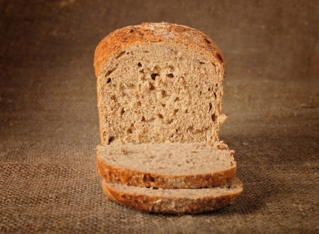 Sliced bread with grains over canvas burlap background photo