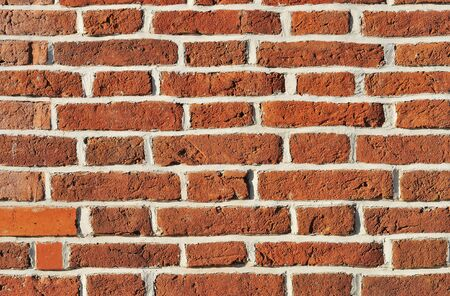 Weathered aged red brickwork wall closeup vintage background