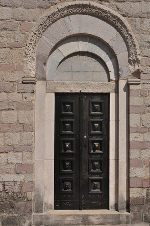 Stone wall with weathered obsolete antique wooden door photo