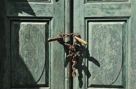Old wooden green paint door with lock and chain photo