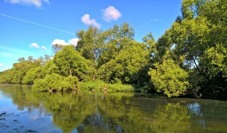 Summer landscape with blue cloudy sky, river, trees and grass Reklamní fotografie