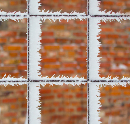 Rusty wire fence covered with frost and hoarfrost with blurred bricks background. Textures. Stock Photo