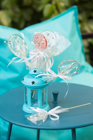 Lollypops in lantern on the turquoise table