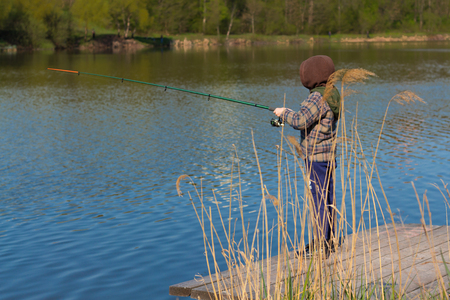 The boy with a fishing rod. Boy on spinning fishing.